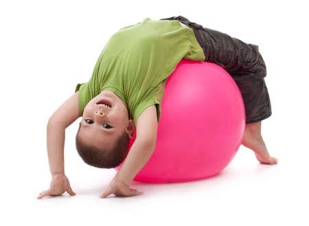 gymnastique: Petit gar�on, faire des exercices de gymnastique avec une balle en caoutchouc grand
