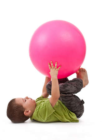 ball stretching: Little boy doing gymnastic exercises with a large rubber ball  Stock Photo