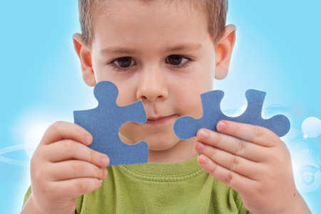 Boy connect puzzles - blue background Stock Photo