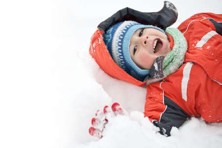 and lies: Portrait of little happy boy lies in snow