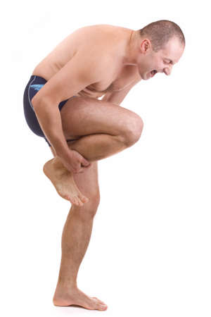 Young man with an expression of severe pain in his leg  . White background.  Stock Photo