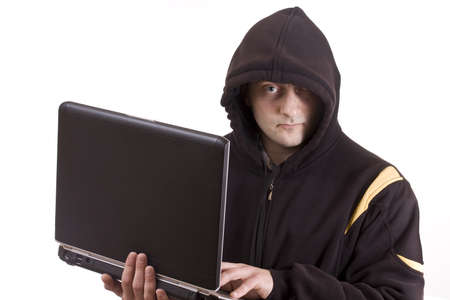 Closeup portrait of a young male thief stealing data from laptop computer  photo