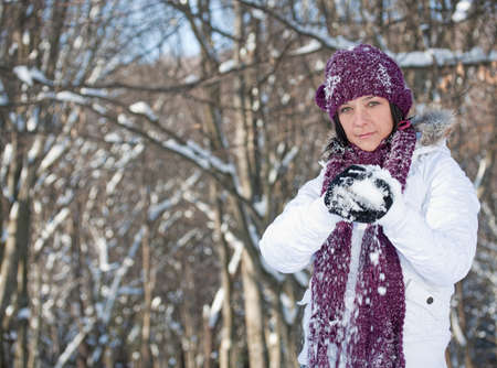 furred: Young woman playing with snowballs in the forest Stock Photo