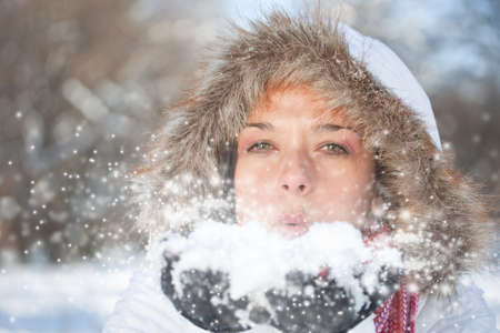 Young woman blowing snow, winter fun