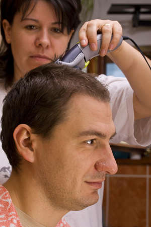 Hairdresser cutting hair with clippers photo