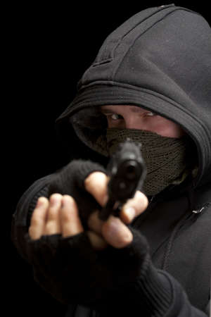 balaclava: Thief with gun aiming into a camera - isolated on black background