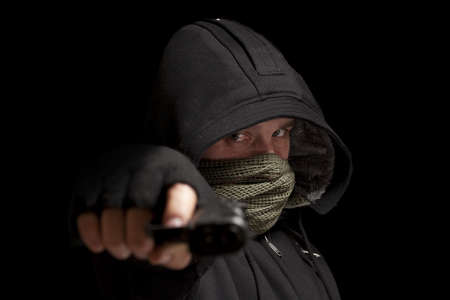 balaclava: Thief with gun aiming into a camera