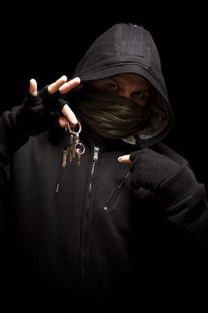 mobster: Thief with keys aiming into a camera - isolated on black background