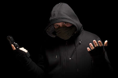 Thief with gun - isolated on black background photo