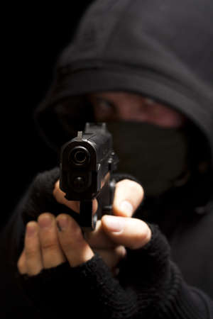 robbery: Thief with gun aiming into a camera - isolated on black background