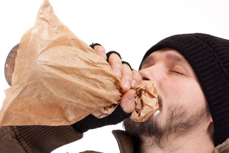 Young homeless man drinking booze from a paper bag  photo