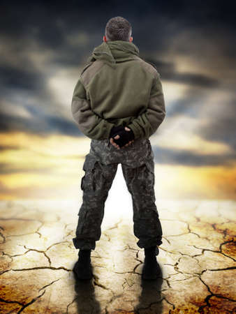 Military standing - back view, looking for apocaliptic sunrise Stock Photo