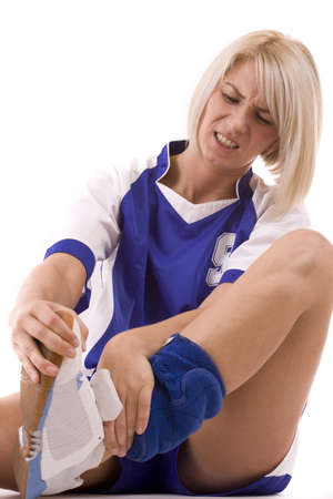 Handball player with an expression of severe pain in his leg. White background.  photo