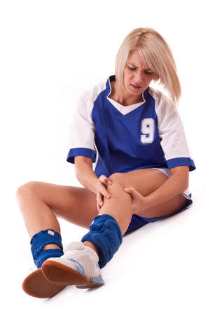 aching muscles: female handball player holding on knee, isolated in white