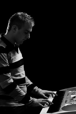boy plays piano, in black background, monochrome Stock Photo - 9295227