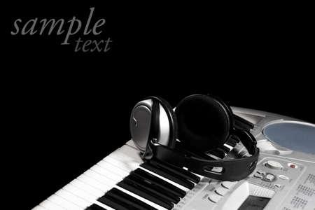 Headphones on keyboard, isolated in black photo