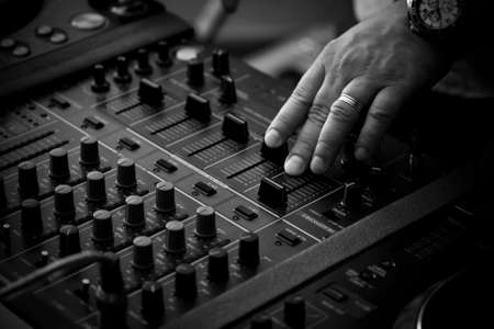 audio mixer: DJ playing music on professional mixing controller