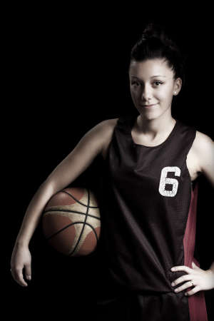 basketball player: Smiling female basketball player holding ball, in black background