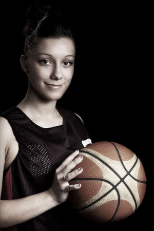 Smiling female basketball player holding ball, in black background photo