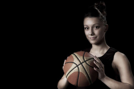Smiling female basketball player holding ball, in black background