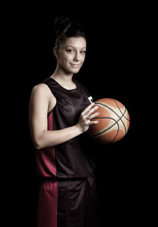 Smiling female basketball player, in black background photo