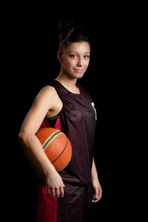 Smiling female basketball player, in black background Stock Photo