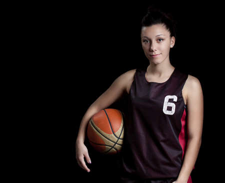 Smiling female basketball player, in black background Stock Photo - 9877221