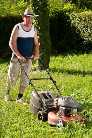 Senior man mowing the lawn photo
