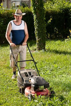 Senior man mowing the lawn Stock Photo