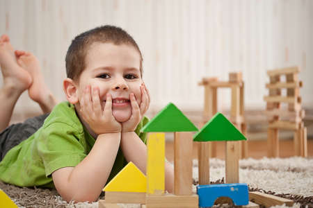 wood blocks: little boy building a house with colorful wooden blocks