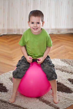 ball stretching: Boy play with large ball in room