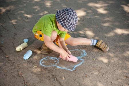 Boy drawing with chalk on asphalt  photo