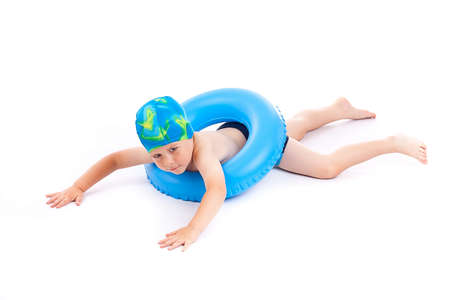 Funny little boy playing with blue life ring in swim caps, isolated in white photo