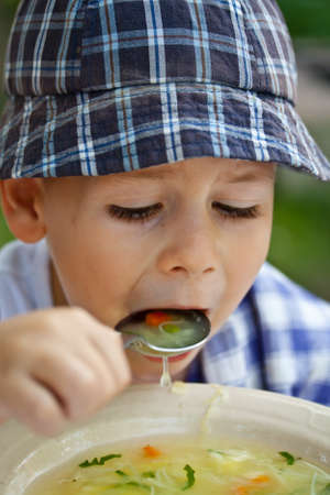 solely: Little boy eating soup solely