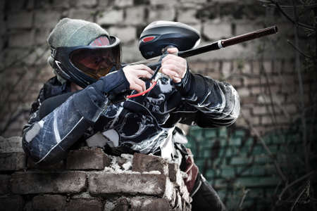 paintball: Paintball player aiming with marker in grunge background