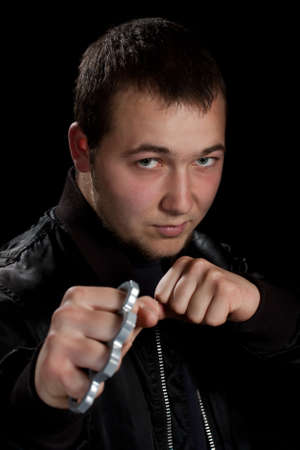 man with brass knuckles in black background photo
