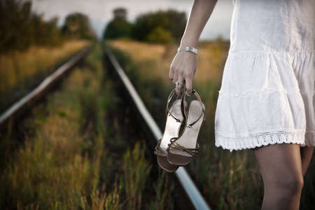 picture of young woman hand with shoes on the railway  Stock Photo