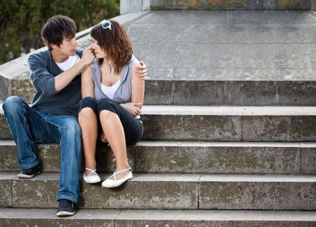 Portrait of young love couple sitting together on steps of a building  photo