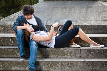 natural love: Portrait of young love couple sitting together on steps of a building  Stock Photo