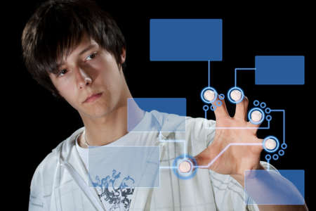 technology metaphor: Man pressing digital button, futuristic technology in black background Stock Photo
