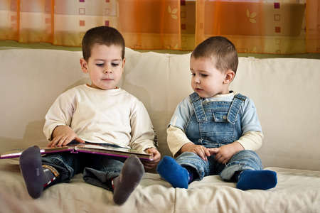 Image of smart children reading interesting book  photo