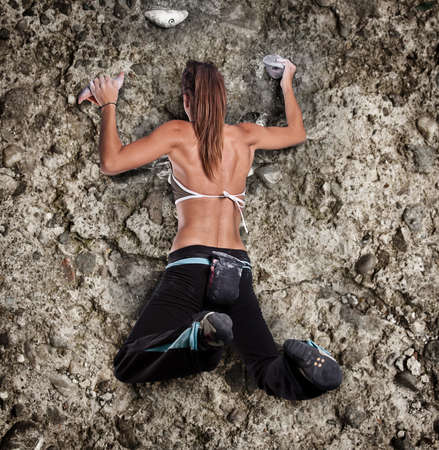 Athletic girl climbing on rock-climbing wall photo