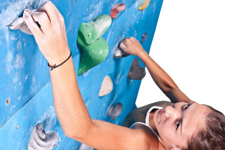 to climb: Athletic girl climbing on an indoor rock-climbing wall  Stock Photo