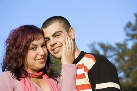 Portrait of love couple embracing outdoor in park looking happy Stock Photo - 10507915