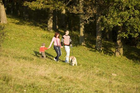 ni�os caminando: Pareja y ni�os que caminan a su perro en la naturaleza