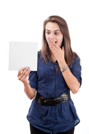 Portrait of a surprised young woman looking at a blank card isolated over white background