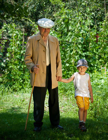 vieux: Portrait de petit gar�on aider un vieil homme sur la marche - en plein air Banque d'images