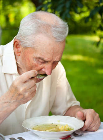 Portrait of a senior man eating a soup outdoor photo
