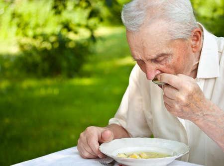 man eten: Portret van een senior man een soep buiten eten Stockfoto
