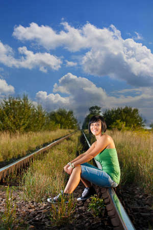 happy girl sitting on the railroad  photo